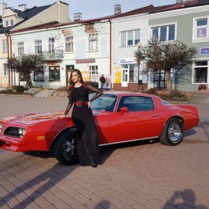 modelka w stroju Fundacji Artystycznej GA MON z Tarnobrzega przy zabytkowym samochodzie