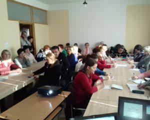 Sala konferencyjna z dwoma stołami, przy której zasiada ok. 30 osób dorosłych