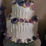 Tort w kolorze białym z fioletowymi kwiatami z cukru