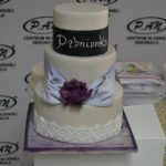 Tort na fioletowej tacy z napisem Dębnianka i fioletową szarfą