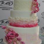 Czteropiętrowy tort w kolorze białym z różowymi kwiatami z cukru
