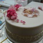 Tort w kolorze białym z figurką niemowlęcia oraz różowymi różami