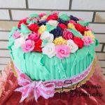 Tort z zielonym lukrem oraz kolorowymi kwiatkami z cukru