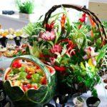 Kosz z sałatką owocową w wyrzeźbionym arbuzie oraz bukiet z artystycznie przyciętych warzyw