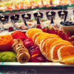 Taca z owocami pokrojonymi na plasterki, w tle desery w szklankach oraz wykałaczki