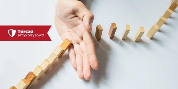 Ręka zatrzymująca domino - plakat Tarczy Antykryzysowej