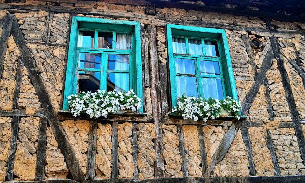 Niebieskie okiennice w starym drewnianym domu